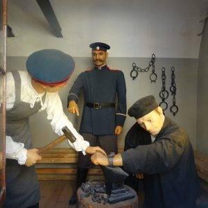 man putting prisoner in shackles