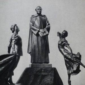 Statue of priest next to 2 people