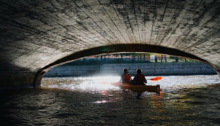 couple in a kayak on the river under the bridge