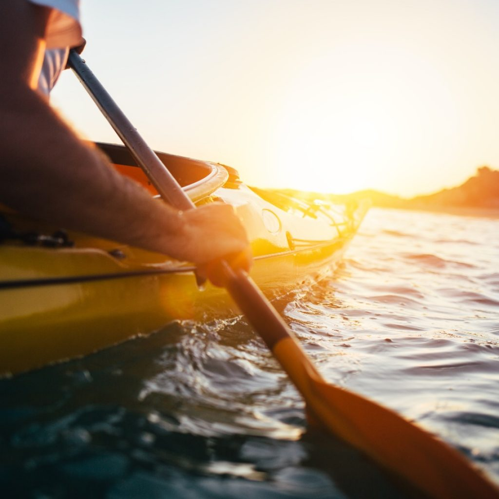 man holding kayak paddle at sunset sea