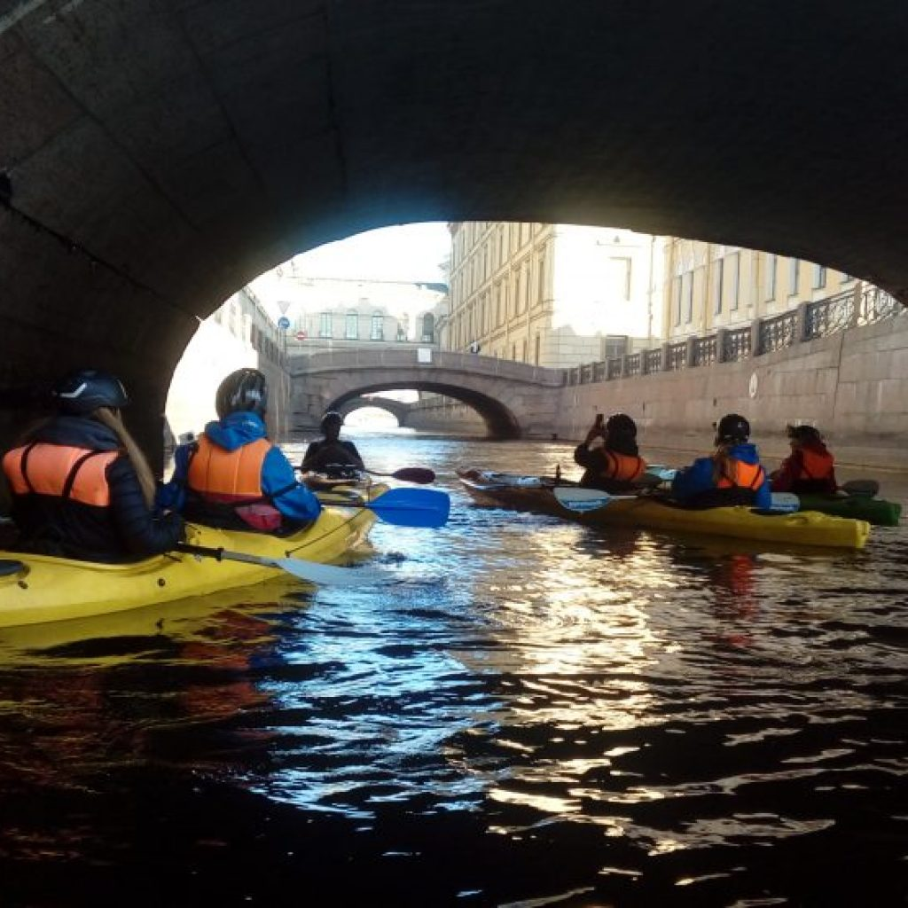group kayaking under bridge of canal